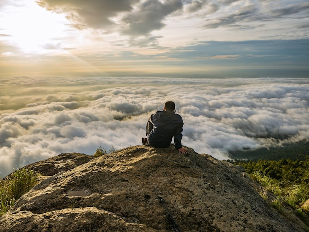 Trekker sitting on the mountain with beautiful sunrise and sea of mist in the morning on khao luang mountain in ramkhamhaeng national park,sukhothai province
