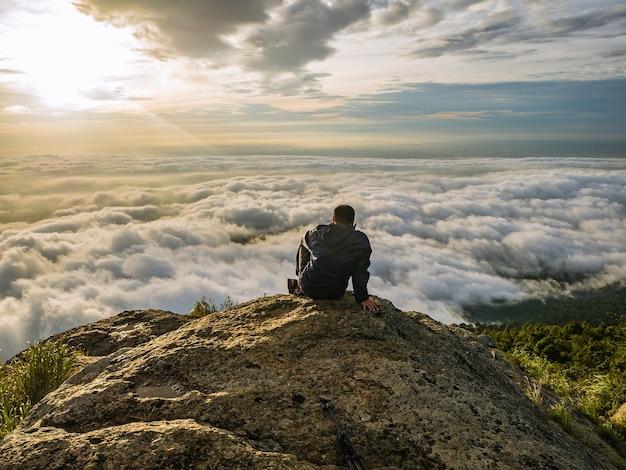Треккер сидит на горе с прекрасным восходом солнца и морем тумана утром на горе кхао луанг в национальном парке рамкхамхенг, провинция сукхотай