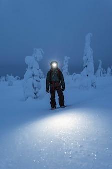 フィンランドの雪に覆われたリーシトゥントゥリ国立公園を歩くヘッドランプ付きトレッカー