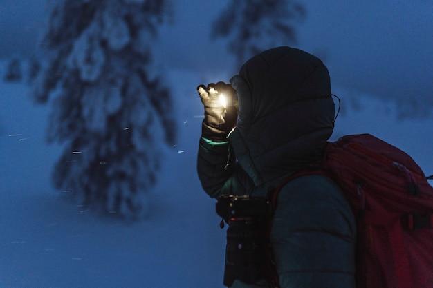 핀란드, 눈 덮인 리시툰투리 국립공원에서 헤드램프를 들고 걷는 트레커