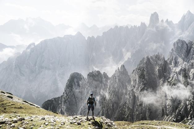 Trekker con uno zaino che si gode una vista sulle montagne nebbiose