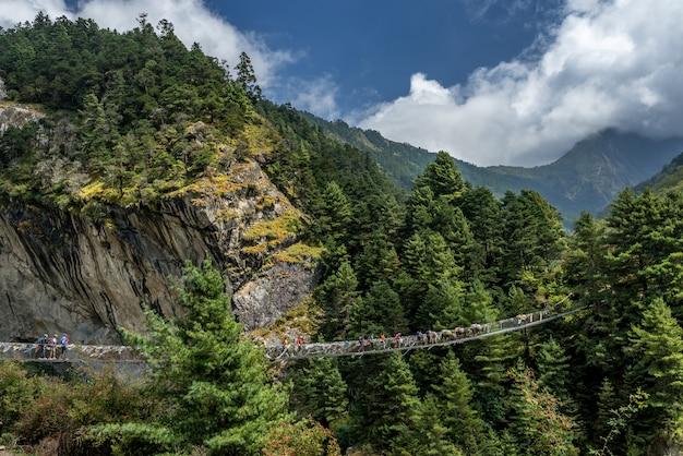 Trekkers crossing suspension bridge in everest region , nepal.