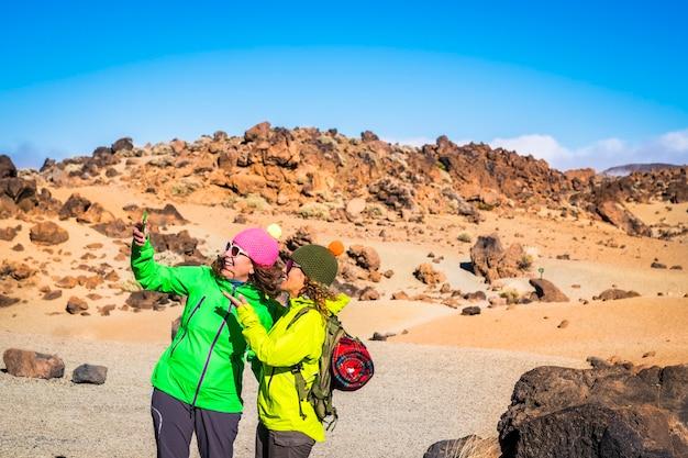 Трекинг и горные экскурсии на свежем воздухе, активность людей с двумя взрослыми женщинами, подругами, делающими селфи вместе, веселыми во время похода, активный образ жизни