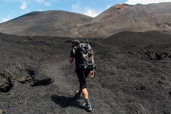 Trekking at peak volcano.Hiker climbing at crater volcano Etna in Sicily