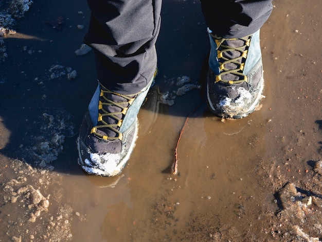 Trekking boots in the muddy spring. the ice melts in the spring, a man walks through puddles on the street, spring weather.