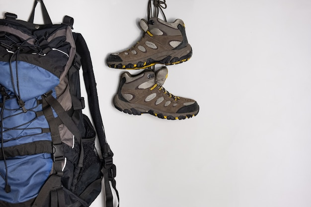 Trekking boots and a tourist backpack on white background. preparing for a hiking trip concept.