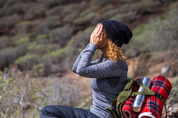 Треккинг женщина в активном отдыхе на свежем воздухе делает какое-то действие рейки - активные люди, любящие природу и окружающий мир - женщина с закрытым лицом и закрытыми руками - концепция путешествия с рюкзаком
