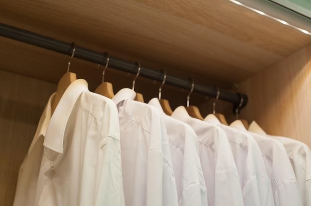 Белые мужские рубашки, висящие на trembler в шкафу