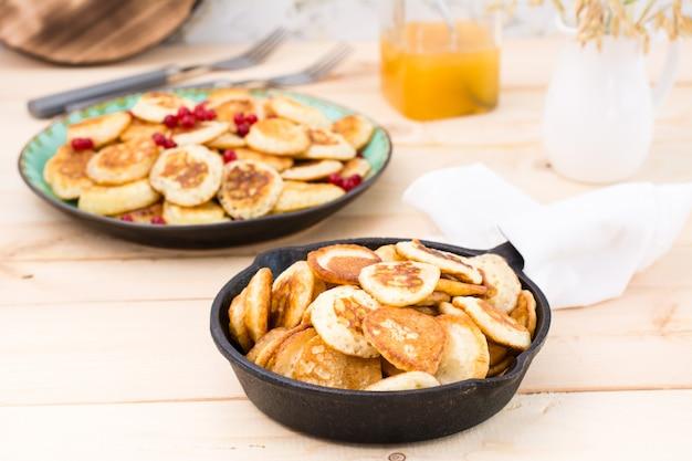 トレンドの朝食。鍋と木製のテーブルの赤スグリとプレートのオランダのミニパンケーキ。