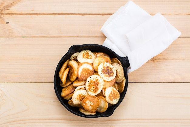トレンドの朝食。木製のテーブルに鍋のクローズアップでオランダのミニパンケーキ。