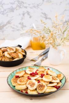 トレンドの朝食。皿の上の赤スグリと木製のテーブルの上のパンとオランダのミニパンケーキ。