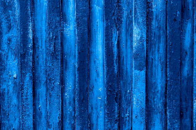 Trend color 2020 classic blue,  peeled wooden fence background for design.