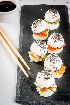 Trend hybrid food. japanese asian cuisine. mini sushi-burgers, sandwiches with salmon, hayashi wakame, daikon, ginger, red caviar. white marble table, with chopsticks, soy sauce. copy space