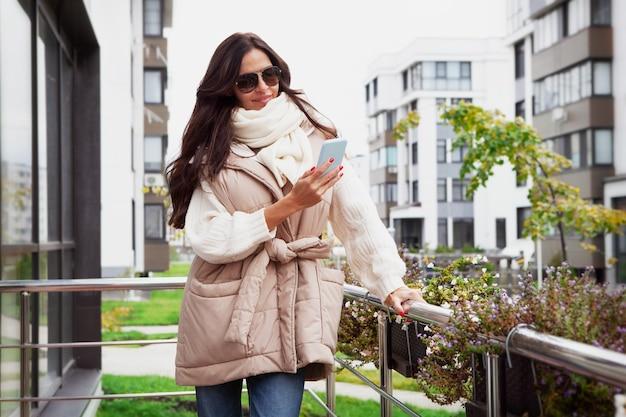 Трендовый наряд на осень или весну модная женщина с длинными волосами в бежевом лоскутном жилете