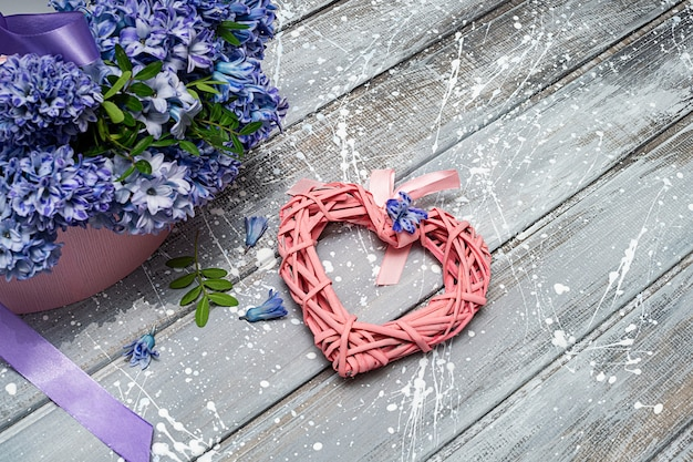 Трендовые весенние цветы гиацинты в коробке и розовое сердечко. понятие любви. скопируйте пространство.