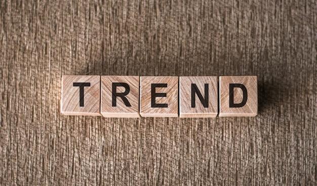 Слово тенденции на деревянных блоках на коричневом фоне