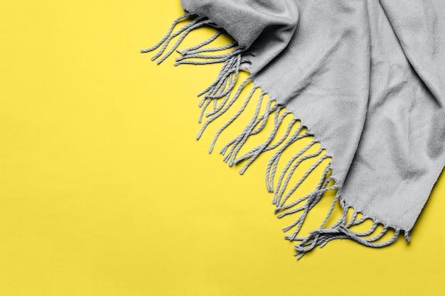 Актуальные цвета 2021 ultimate grey и illuminating. серый шарф с кисточками на желтом фоне. минимальный зимний или осенний фон для вашего дизайна.