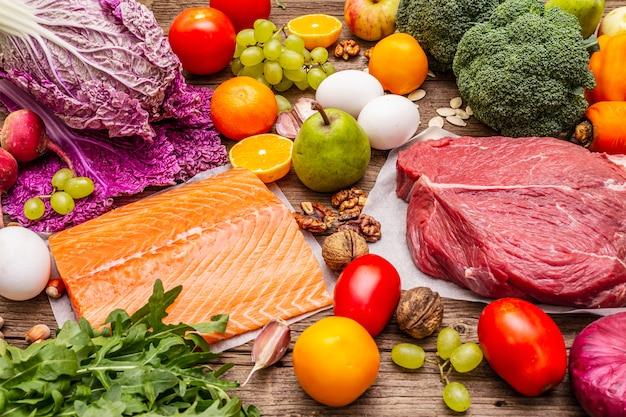 Тенденция к палео-пеганской диете. концепция здорового сбалансированного питания. набор свежих продуктов, сырого мяса, лосося, овощей и фруктов