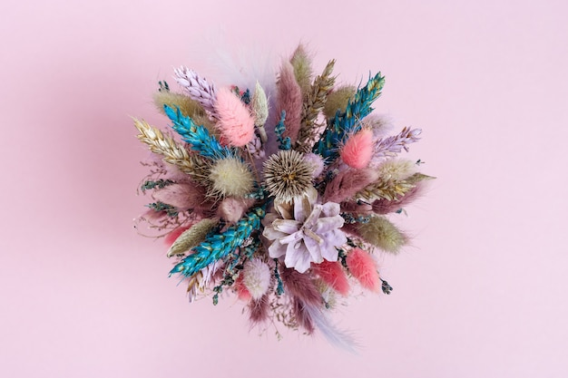 Trendly beautiful flowers bouquet pink and lilac colored wiht dried plants, flower, grass. handmade floral decoration. top view.