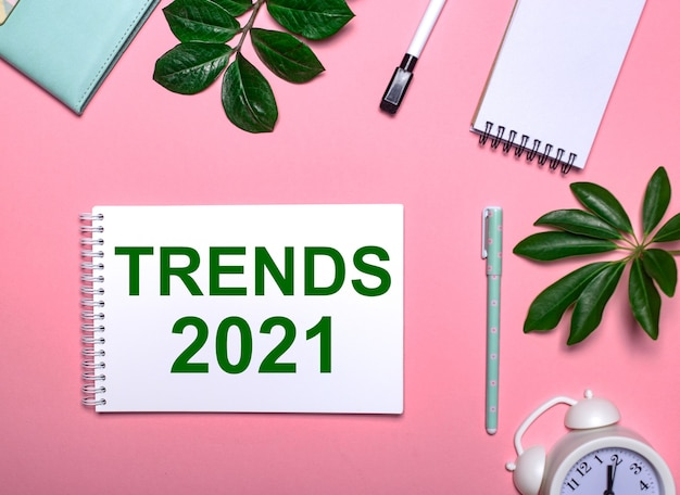 Trends 2021 is written in green on a white notepad on a pink surface surrounded by notepads, pens, white alarm clock and green leaves. educational concept