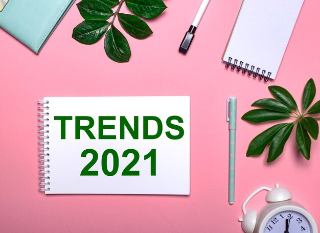 Тренды 2021 написано зеленым на белом блокноте на розовой поверхности в окружении блокнотов, ручек, белого будильника и зеленых листьев. образовательная концепция