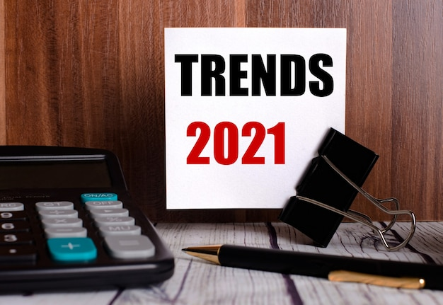 Trends 2021 is written on a white card on a wooden wall next to a calculator and pen.