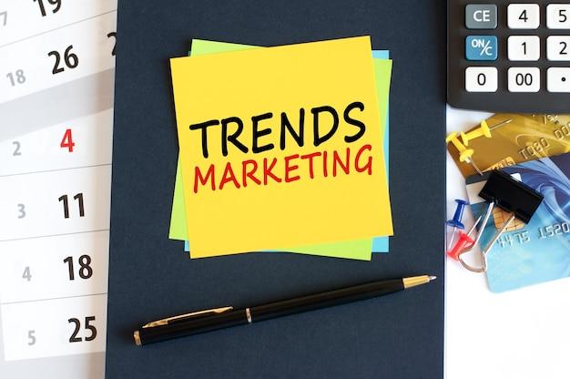 Тенденции маркетинга, текст на желтой бумаге квадратной формы на синем фоне. блокнот, калькулятор, кредитные карты, ручка, канцелярские товары на рабочем столе. концепция бизнеса, финансов и образования.