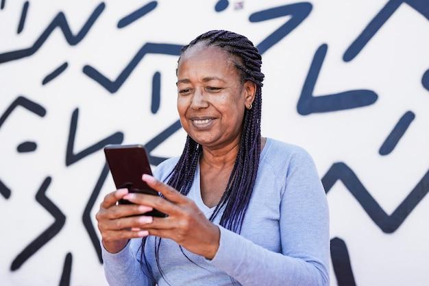 黒と白の背景を持つ街で携帯電話を使用してトレンディなアフリカ系アメリカ人の年配の女性-年配の黒人女性は技術を楽しむ