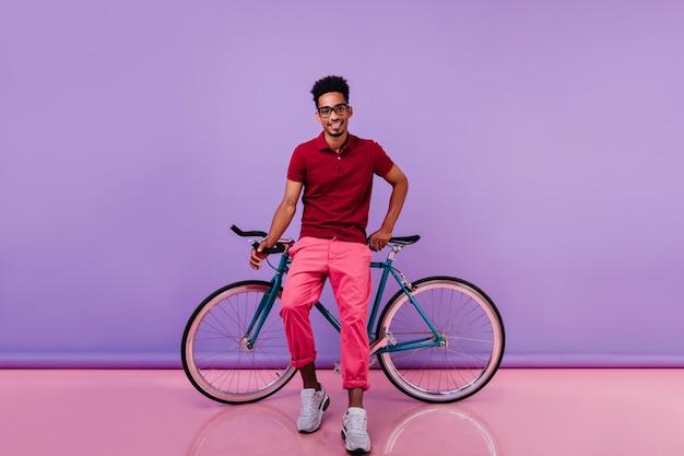 自転車の近くでポーズをとる白い靴のトレンディなアフリカの男。時間を過ごして笑顔の明るい黒人男性。