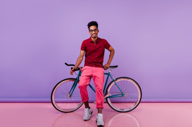 Trendy african guy in white shoes posing near bicycle. smiling blithesome black man spending time.