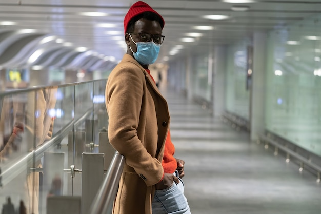 Trendy african hipster man looking at camera, standing in airport terminal, wear face mask. covid-19