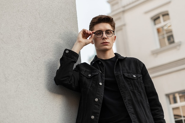 유행 미국 남자 패션 모델은 거리에서 빈티지 안경에 넣습니다. 도시에 흰색 건물 근처 헤어 스타일으로 t- 셔츠에 세련 된 데님 블랙 재킷에 거리 초상화 유행 젊은 남자.