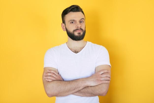 Модный и стильный серьезный красивый бородатый мужчина в белой футболке со скрещенными руками позирует