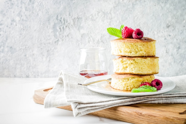 Trendy asian food, fluffy japan souffle pancakes, hotcakes with maple syrup and raspberry light concrete table