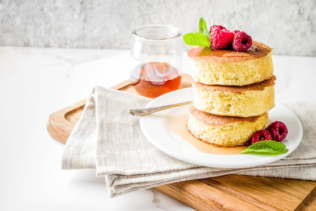 Trendy asian food, fluffy japan souffle pancakes, hotcakes with maple syrup and raspberry