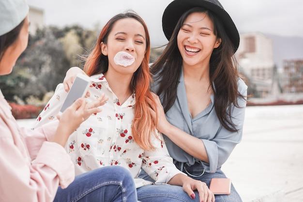 Trendy asian girls making video story for social network app outdoor