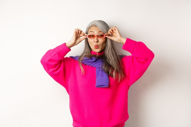 Donna anziana asiatica alla moda in occhiali da sole, labbra pucker e guardando sorpreso alla macchina fotografica, fissando stupito l'offerta speciale, in piedi su sfondo bianco.