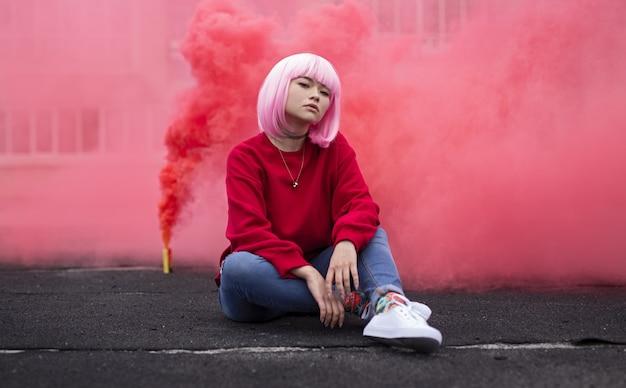 두꺼운 붉은 연기 앞 바닥에 앉아 유행 아시아 십대