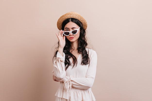 Trendy asian woman looking through sunglasses. front view of joyful chinese lady in straw hat.
