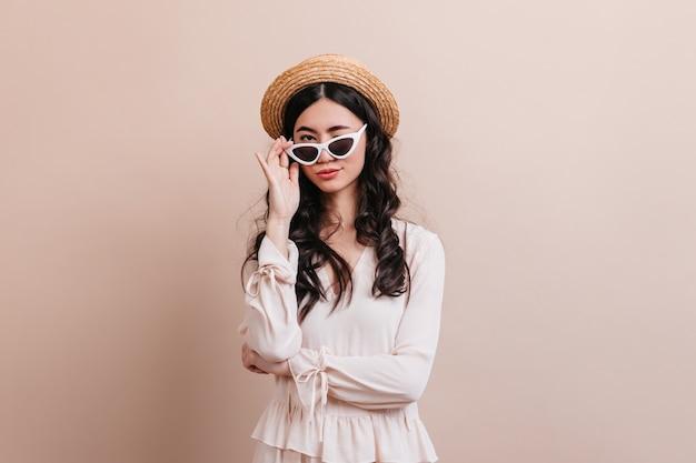 サングラスを通して見ているトレンディなアジアの女性。麦わら帽子をかぶったうれしそうな中国人女性の正面図。