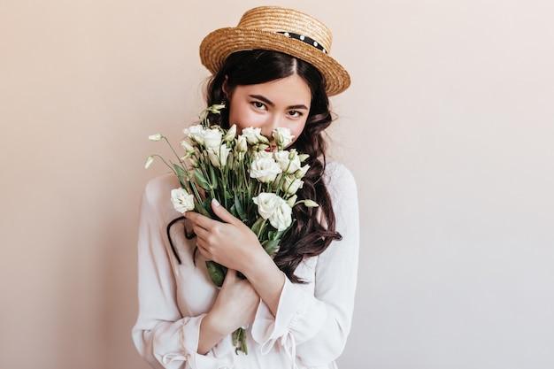 花を嗅ぐトレンディなアジアの女性。白いトルコギキョウの花束を保持しているロマンチックなブルネットの若い女性。