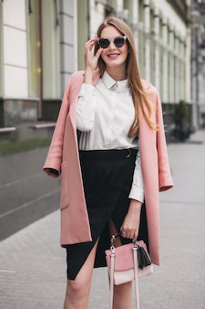 Trendy attractive stylish smiling rich woman walking city street in pink coat