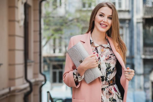 Модная привлекательная стильная улыбающаяся женщина гуляет по городской улице в розовом пальто весенней модной тенденции, держащей кошелек