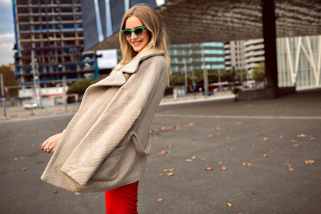 Модный осенний модный портрет стильной молодой женщины, позирующей возле здания современной архитектуры, в хипстерском деловом костюме и пальто, винтажных солнцезащитных очках, тонированных цветах.