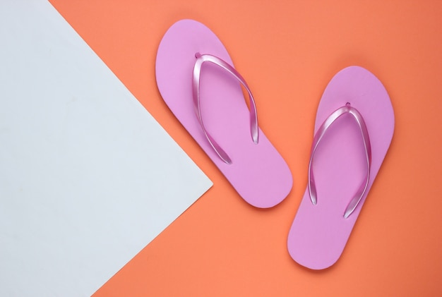 Trendy beach pink flip flops on coral white paper background. copy space. top view