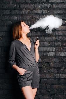 Модная красивая девушка курит без табака сигарету, выдыхая большие облака дыма. одет в модную одежду.