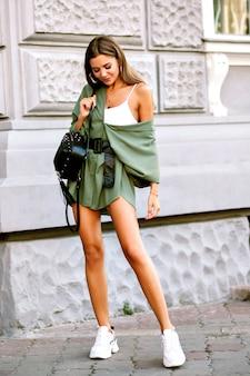 Bellissima modella alla moda in posa per strada, con indosso un abbigliamento casual minimalista