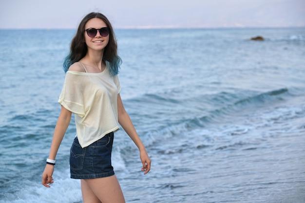 선글라스와 바다 해변을 따라 걷는 반바지에 긴 색깔의 파란 머리를 가진 유행 아름다운 십 대 소녀