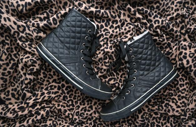 Модные черные кожаные стеганые кроссовки на фоне животных с принтом. черно-золотистый леопардовый гепард пятнает фактурную ткань. модная обувь обувь концепция. flatlay.