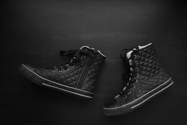 Модные черные стеганые кроссовки, ходить на доске фоне. минималистский черный, темный режим, концепция fasion shoes. плоская планировка,